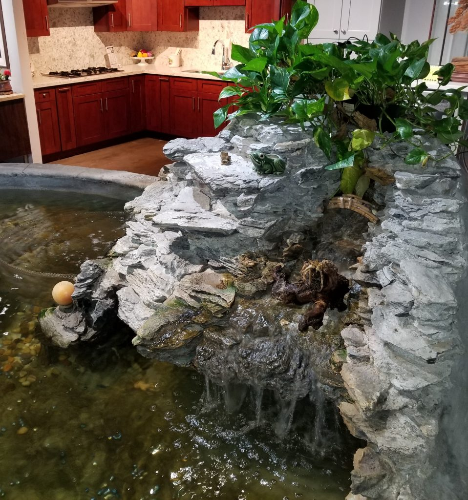 indoor-water-fountain-cascading-waterfall-over-rocks-leading-to-koi-pond